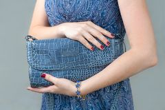 Blue closed clutch in womens hands Royalty Free Stock Image