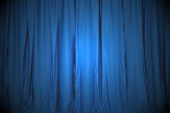 Blue closed the curtain, lit by a spotlight Royalty Free Stock Images