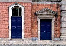 Blue closed doors on a brick facade of a building stock photos