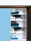 Blue closet. Open closet with blue color home decor textile on shelves royalty free stock images
