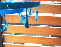Blue clothespin hanging and wooden slat as background. Blue clothespin hang on clothesline which is in front of wooden slat as background Royalty Free Stock Photography