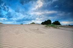 Blue clouded sky over sand dunes Stock Photos