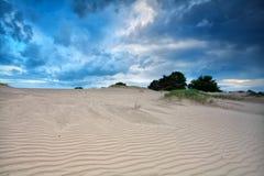 Blue clouded sky over sand dunes Stock Photos