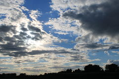 Blue clouded sky with tree line at horizon Stock Images
