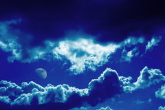Blue clouds and moon background. Dramatic dark blue clouds and moon background stock photo