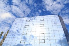 Blue clouds and trees are reflected in the glasses of windows of a modern building. Bottom view Royalty Free Stock Photo