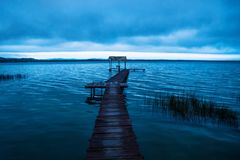 Cloudscape behind dock along the lake shore before sunset, El Remate, Peten, Guatemala. Blue cloudscape behind dock along the lake shore before sunset in blue Royalty Free Stock Images