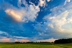 Blue cloudscape over green meadows in the countryside. Patchy clouds over fields Stock Photo