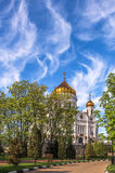 Blue cloudy sky above a golden orthodox church in summer Stock Photos