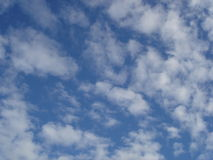 Blue cloudy sky abstract background. Texture of bright blue with soft fluffy white clouds sky in Russia Stock Image