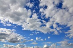 A blue cloudy sky with many small clouds blocking the su. N Royalty Free Stock Image