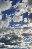 A blue cloudy sky with many small clouds blocking the su. N Stock Image