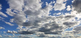 A blue cloudy sky with many small clouds blocking the su. N Stock Photography