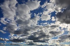 A blue cloudy sky with many small clouds blocking the su. N Stock Photos