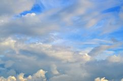 A blue cloudy sky with many small clouds blocking the su. N Stock Images