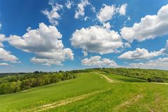 Blue cloudy sky over green hills and country road. Bieszczady mountain range, Poland royalty free stock photography