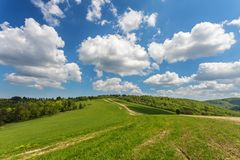 Blue cloudy sky over green hills and country road. Bieszczady mountain range, Poland stock image
