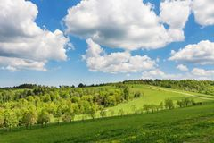 Blue cloudy sky over green hills and country road. Bieszczady mountain range, Poland royalty free stock photos