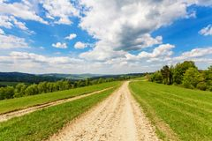 Blue cloudy sky over green hills and country road. Bieszczady mountains, Poland Royalty Free Stock Photos