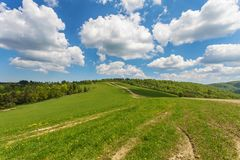 Blue cloudy sky over green hills and country road. Bieszczady mountain range, Poland stock images