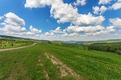 Blue cloudy sky over green hills and country road. Bieszczady mountain range, Poland stock photo