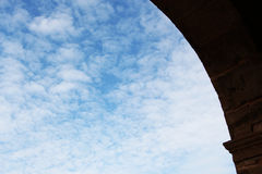 A blue cloudy sky through a stone arch Royalty Free Stock Image