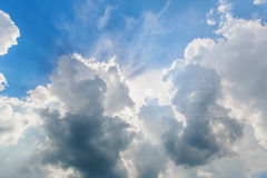 Blue cloudy sky with sun rays Stock Photos