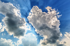 Blue cloudy sky with sun rays Royalty Free Stock Image
