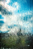 Blue cloudy sky through wet glass Royalty Free Stock Photography