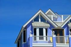 Blue Coastal Home. Gabled blue coastal home with balcony under blue sky Royalty Free Stock Photo