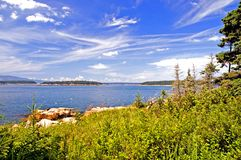 Blue coastline of Maine. A view of the beautiful blue sky, clouds and islands along the coastline of Maine near Schoodic Point, on a clear, summer day Stock Photography