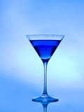 Blue cocktail. Blue drink  on a blue background in a cocktail or martini glass Stock Images