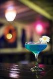 Blue cocktail drink in dark bar interior Stock Photos