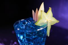 Blue cocktail with fruits and ice cubes stock images