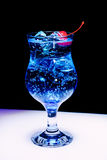 A blue cocktail with ice and cherry. In the club on dark background Royalty Free Stock Image