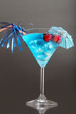 Blue cocktail with ice and umbrella Royalty Free Stock Images