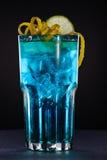 Blue cocktail with iceBlue cocktail with ice with orange and lemone. Blue cocktail with ice with orange and lemone on black Stock Photo