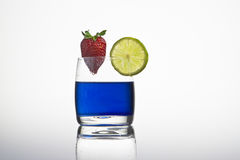 Blue cocktail with lemon. A blue cocktail with lemon and strawberry Stock Photo