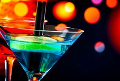 Blue cocktail with light disco bokeh background with space for text Stock Image