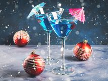 Blue cocktail in martini glass for Christmas party. Blue cocktail in martini glass with umbrella and cherry. Festive drink for Christmas holiday party. Snow fall royalty free stock photos