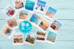 Blue cocktail and photos of beautiful moments of happy summer holidays in Greece. On the light blue wooden background. Horizontal. Top view. Daylight stock images