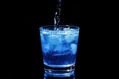 Blue cocktail pouring in a glass Stock Images