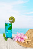 Blue cocktail and sandy beach Royalty Free Stock Images