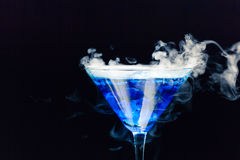 Blue cocktail with splash and ice vapor. On black background Stock Photography