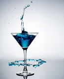 Blue cocktail with splash on white background Royalty Free Stock Photo