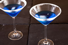 Blue cocktails. Two long-stemmed cocktail glasses with salted rims Royalty Free Stock Photos