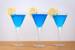 Blue cocktails and lemon slice. Three blue cocktails in stem glasses with sugared rims and sliced lemons stock photo