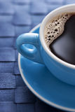 Blue Coffee Cup. A blue coffee cup full of black coffee on a blue background Royalty Free Stock Photography