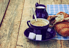 Blue coffee cup, milk jug and croissant with chocolate filling Royalty Free Stock Photo