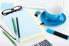 Blue coffee cup and office supplies royalty free stock photo